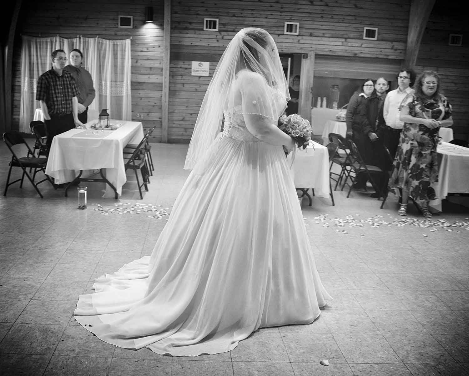 The bride walks down the aisle while the families stand at their tables. photos by Brianna Bivens - 2016