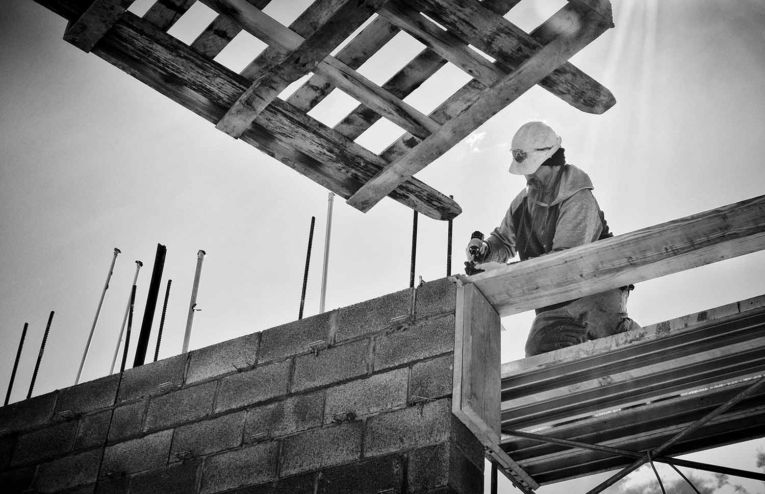 David Mould drills a board into place at a construction site. photo by Jared Sebby - 2016