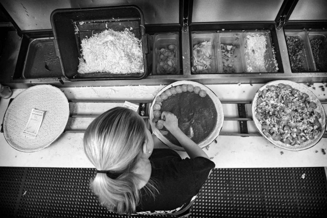 Ciarra Wallace places toppings on a pizza at Charley's Pizza Parlor. photo by Austin Perryman - 2018