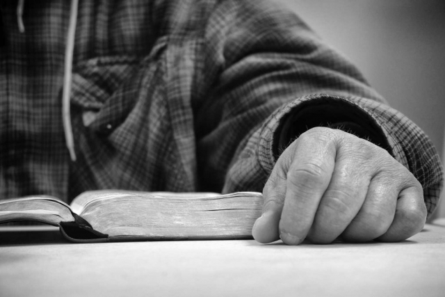 Bill Finn reads his Bible on a quiet Saturday morning at the New Horizon's Homeless Shelter. photo by Samantha Robinson - 2018