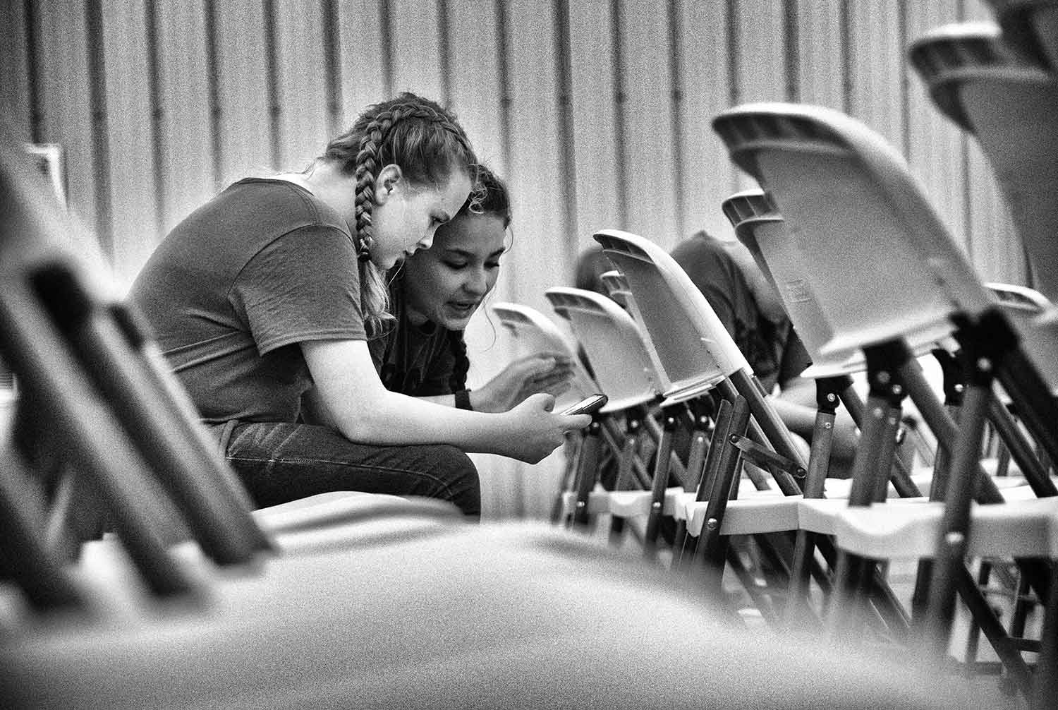 Keylyn (13) and Elisa (12), scroll through messages as they wait for the Break the Cycle church service to start. photo by Caitlyn Jordan - 2019