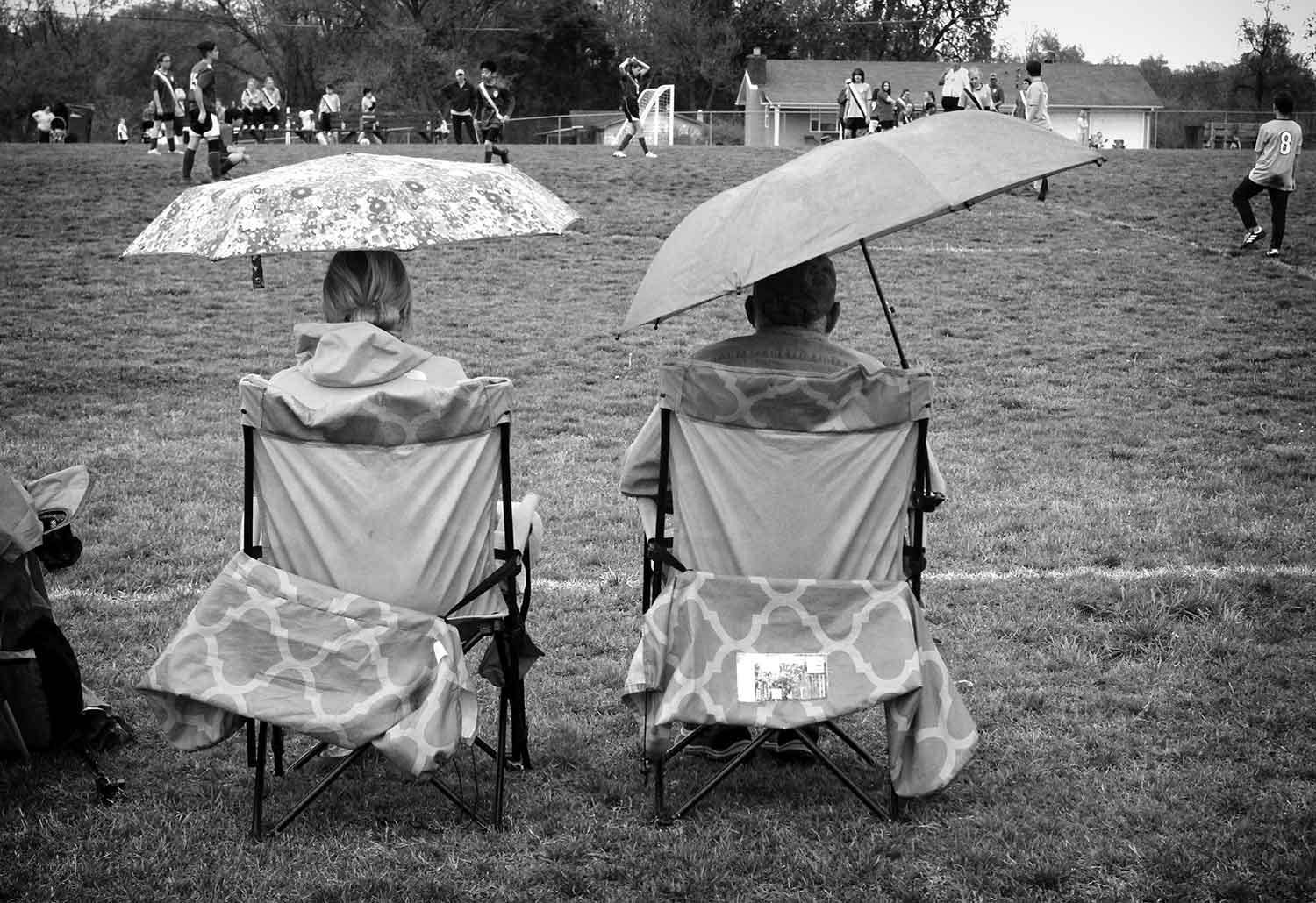Two family members endure the rain and chilly weather as they watch a soccer game at LaFollette Elementary School. photo by Chelsea Babin - 2019