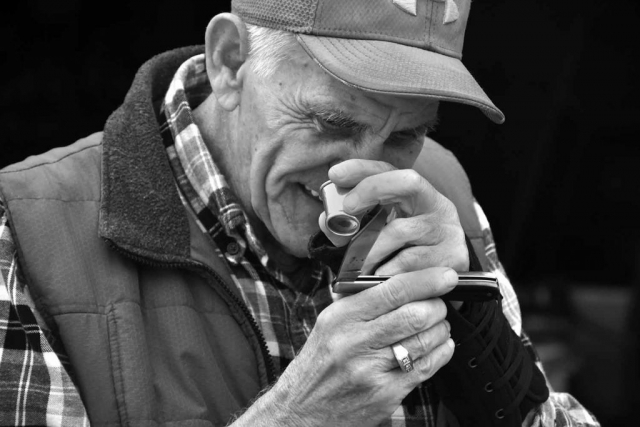 Whit Goins uses a magnifier scope to check for the details on a pocket knife. photo by Jules Morris - 2019