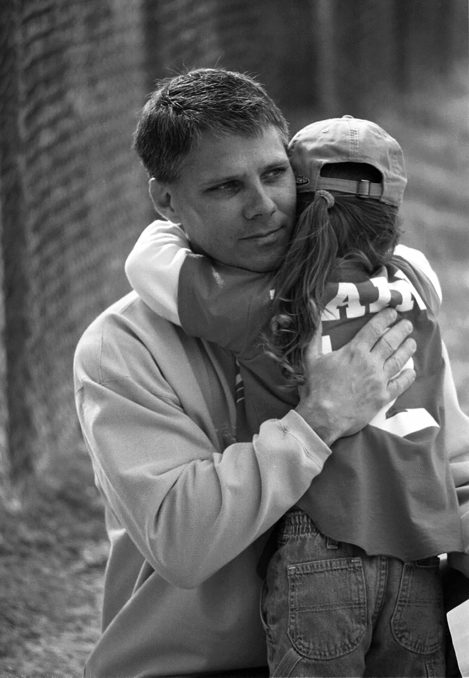 Clint Bane gives his daughter, Brooke, a hug before she goes to bat. photo by Alison Church - 2001