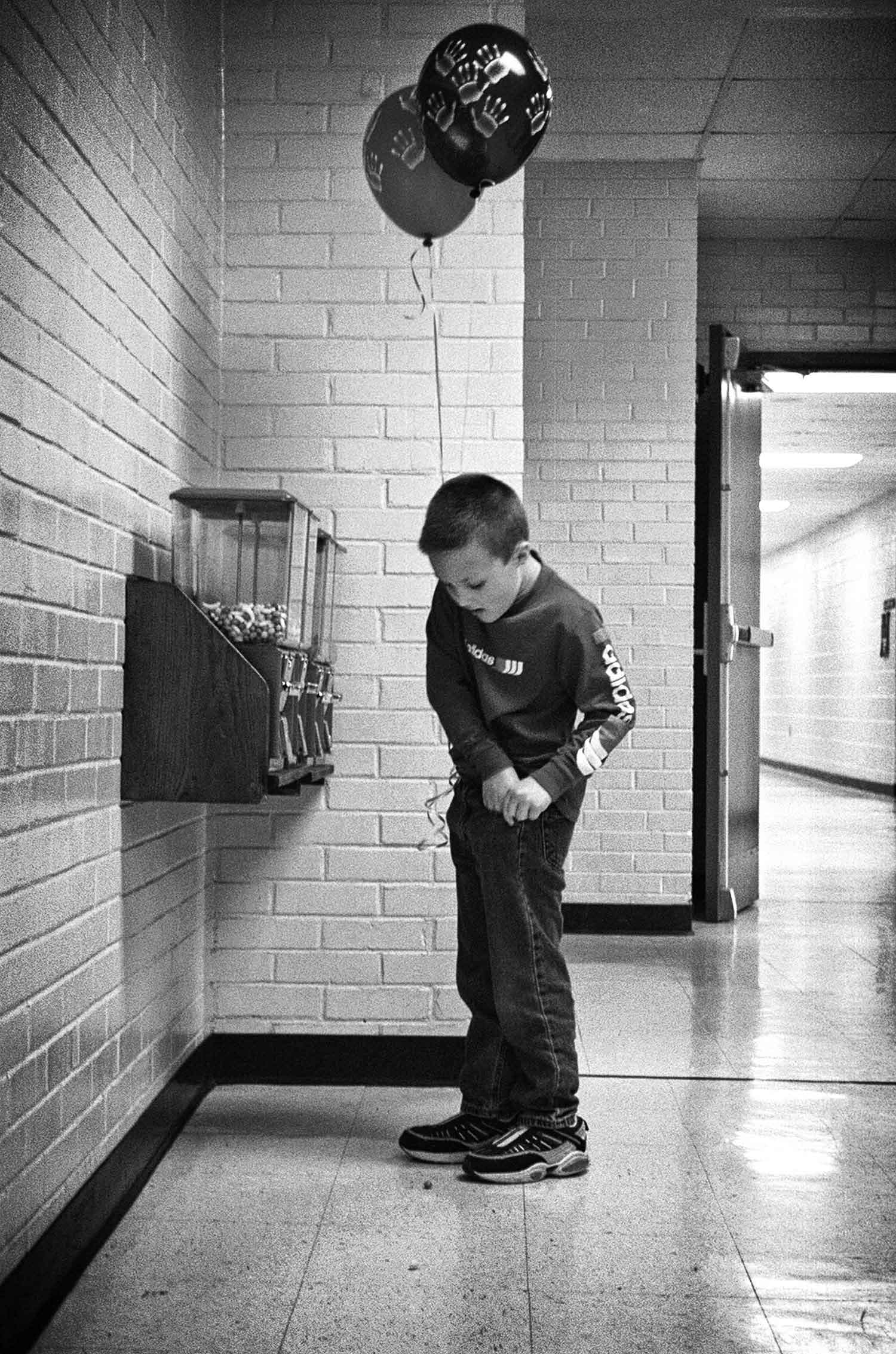 Balloons and candy - what more could a kid want? Kindergartener Seth Pebley digs for change in the hallway of Valley View Elementary. Photo by Jessica White - 2003