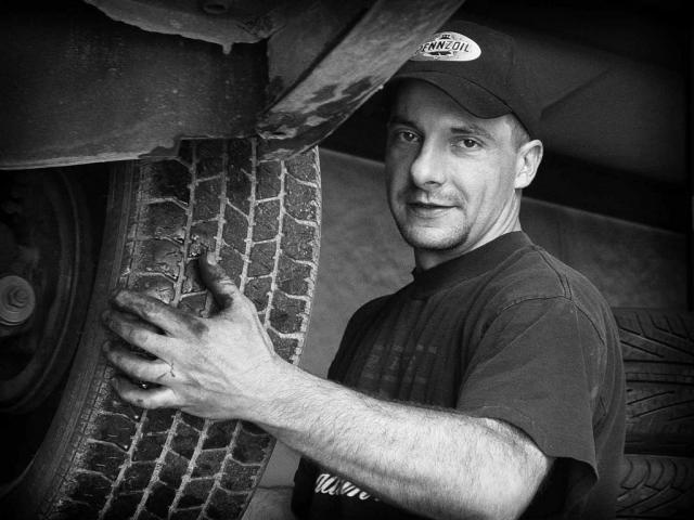 John Womble removes tires from a car at Minton's Tire Service. Photo by Kristi Davis - 2006