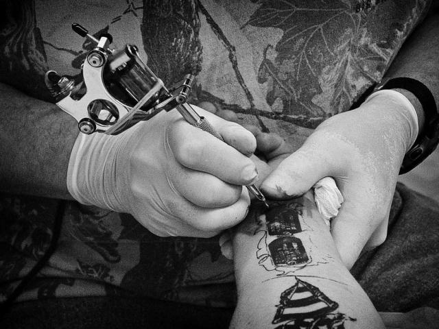 Donnie Silcox tattoos Richard Jones' dog tags on his forearm at DJ's Tattoo. photo by Kristi Davis - 2006
