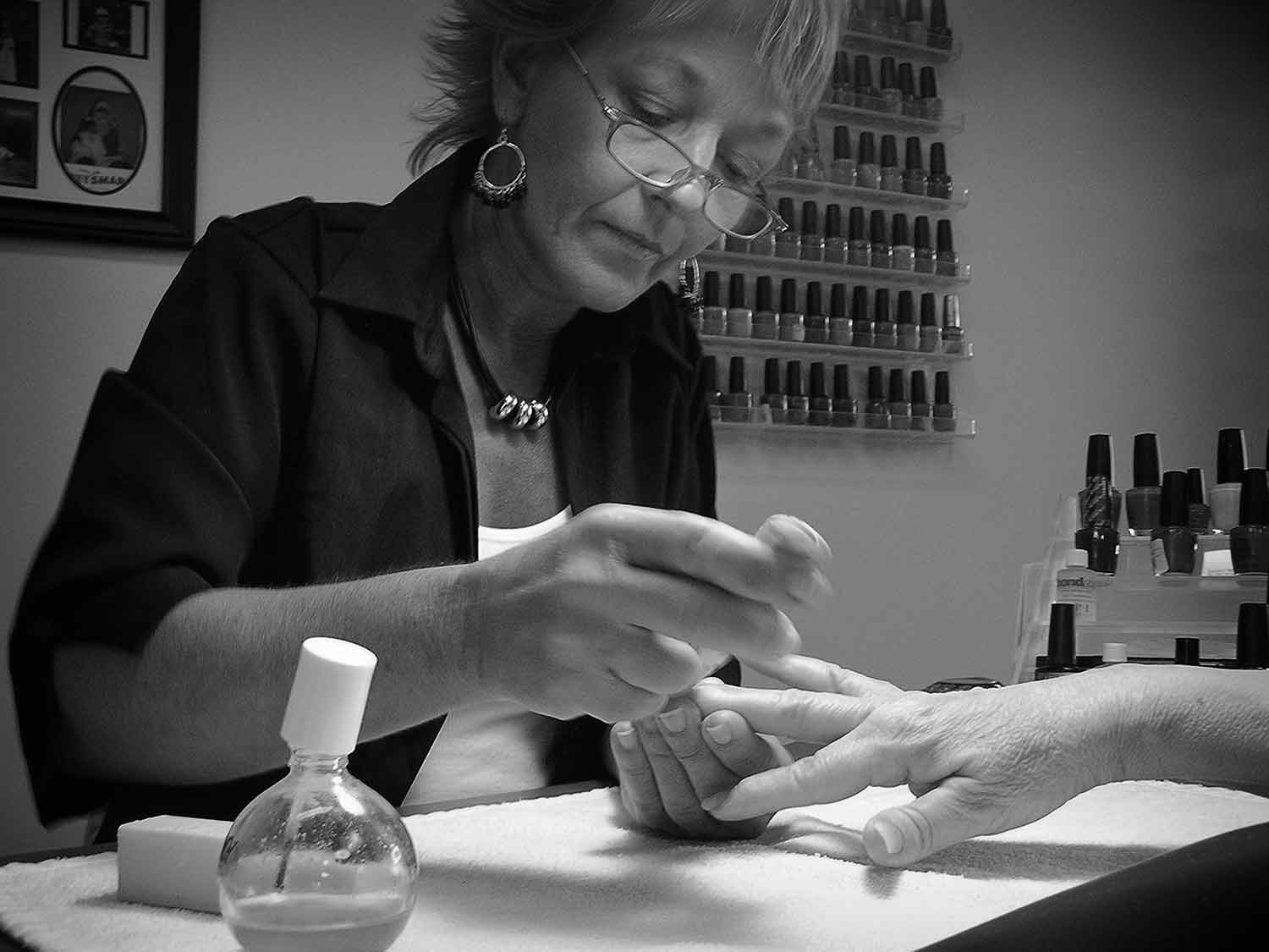 Susie Nelson, co-owner of Creative Expressions, buffs a client's nails. photo by Lisa Schohl - 2007