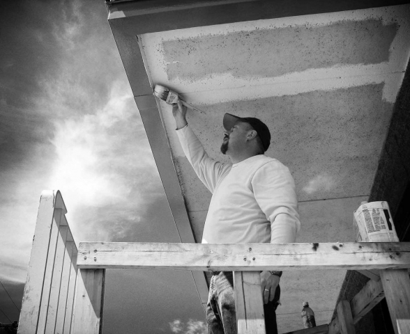 Adam Ivey lifts fl oorboards onto the base of a houseboat he is helping to build for coowners Herbert McGhee and Bob Stormer. photo by Ashley Yeager - 2007