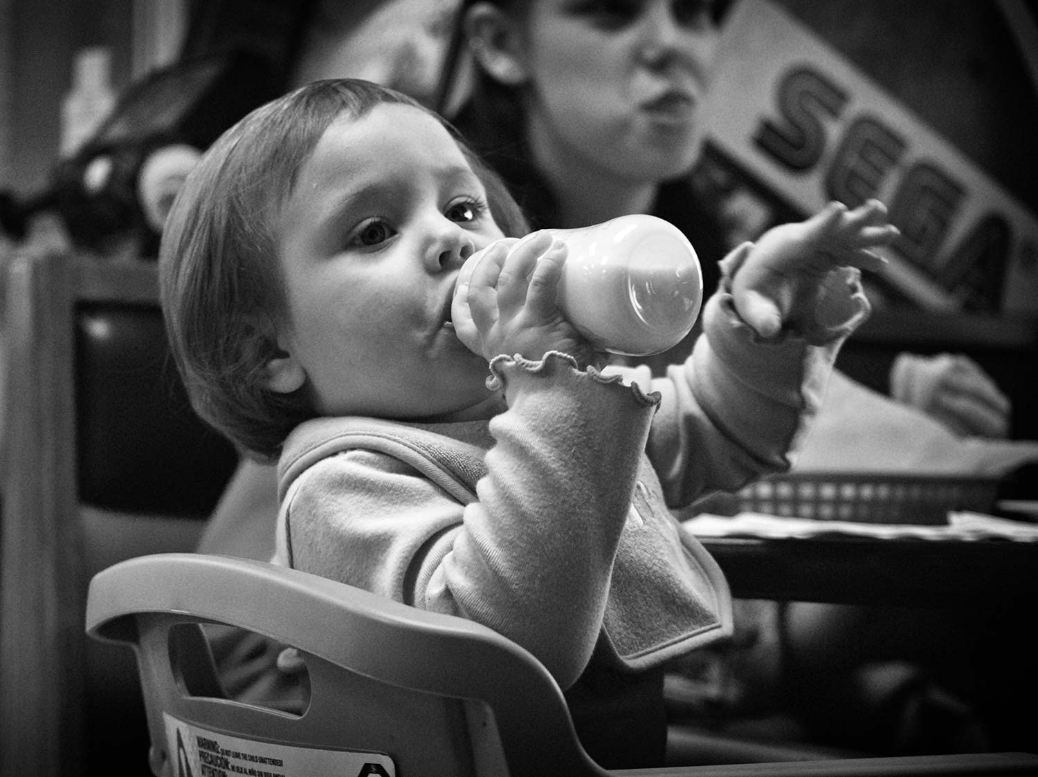 1-year-old Ryleigh Weltch drinks from her cup while admiring customers in Charley's Pizza. Photo By Demetric Banahene. - 2008