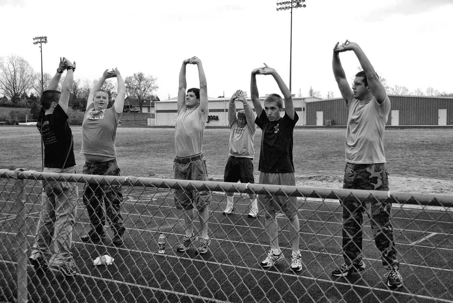 Left To Right: Robert Sopha, Adam Hunter, Tyler Allen, Col. Salveson, Noah Carr, and J. Jeffers. Part of the Raiders team stretches in preparation for a ROTC two-and-a-half mile run. photo by James Bolton - 2009