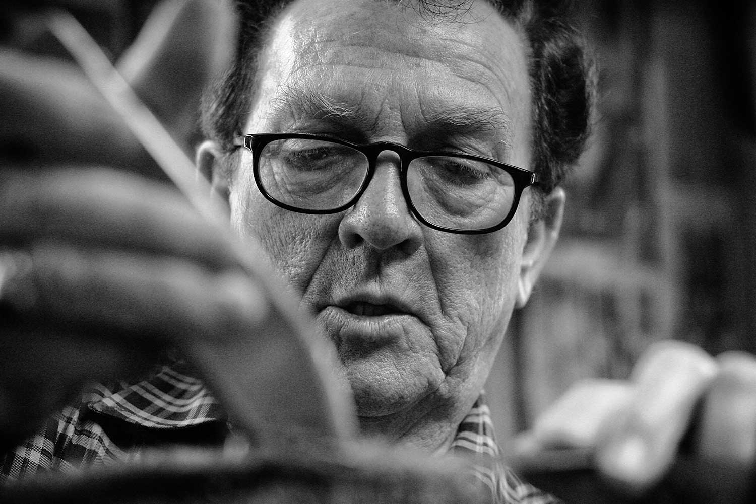 """Ray """"The Barber"""" Beeler focuses intently on the task at hand--telling stories and entertaining his customers. photo by Ben Moser - 2009"""