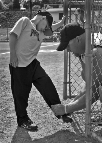 Rick Berry (right) helps his son Landon Berry (left) get ready for his little league baseball game. photo by Stephanie Myers - 2010