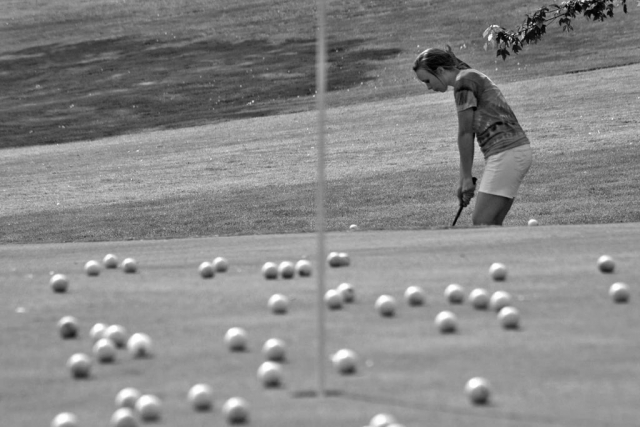 Lindsay Taylor attempts a chip shot at the green. photo by Andy Hayes - 2010