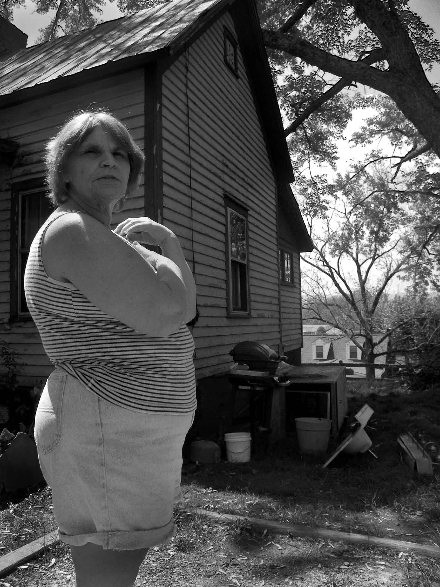 Kathy Carroll Jones is sifting through the ashes of a mobile home that caught fire to salvage scrap metal.  photo by Jonathan Kahler - 2010