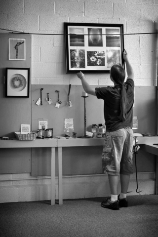 Chris Hill hangs his photographs at Artist Village. photo by Kelsea Hickman - 2012