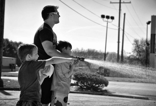 Landon and Noah Francis help their dad Jesse rinse off a car during an Autism Awareness event. photo by Molly Morgan - 2013