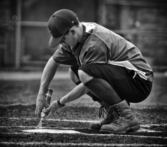 Assistant Coach Brian Miracle stripes home plate prior to the game. photo by Parker Eidson - 2014