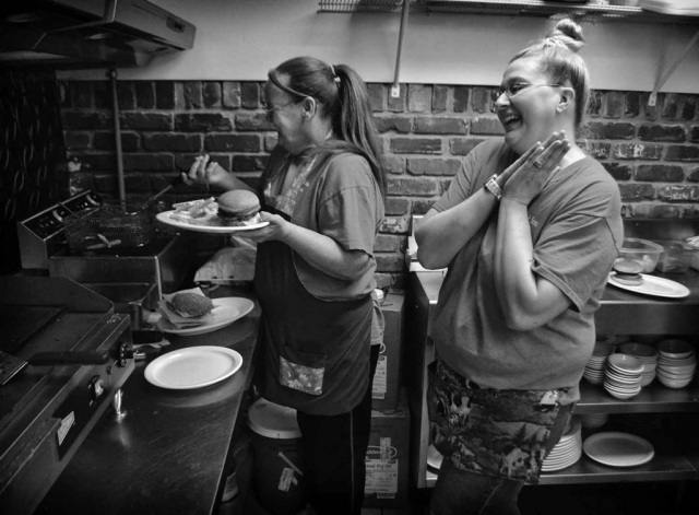 Diane Collins and Chris Goins share a laugh while preparing food at Katie's Carry Out & Catering. photo by Alexandra Harper - 2014