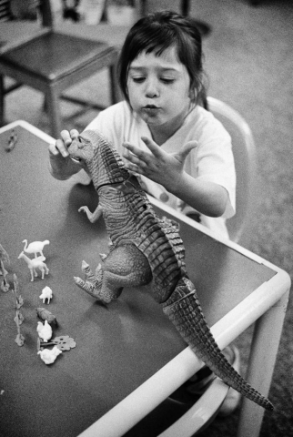 While her mother looks for books in the LaFollette Public Library, Alyssa Jacoby finds the toys to be more entertaining. Photo by Heather Spurgeon - 1995