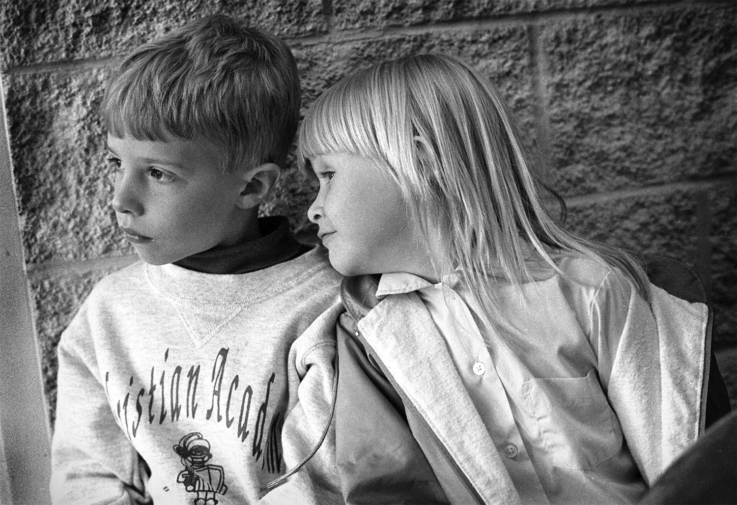 Waiting for their ride home after a long day at school, Will Ellison and Kelsey Leach look outside to see if their parents have arrived yet.  photo by Joshua Brown - 1997