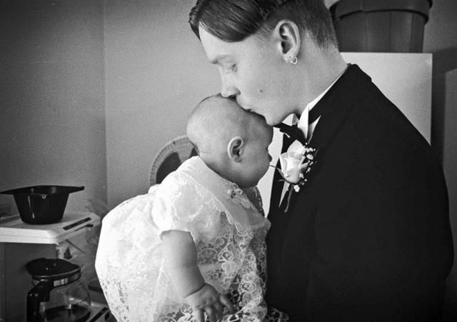 Groom, Steven Pratt kisses his baby.  photo by Joshua Brown - 1997