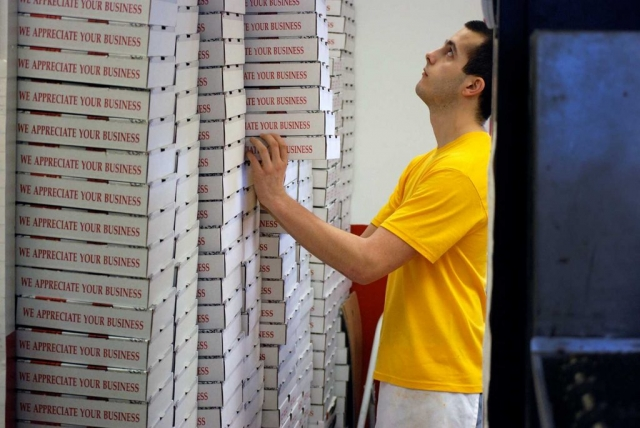 Robby Gross cautiously balances pizza boxes in preparation for a busy day at Charley's Pizza. photo By Demetric Banahene - 2008