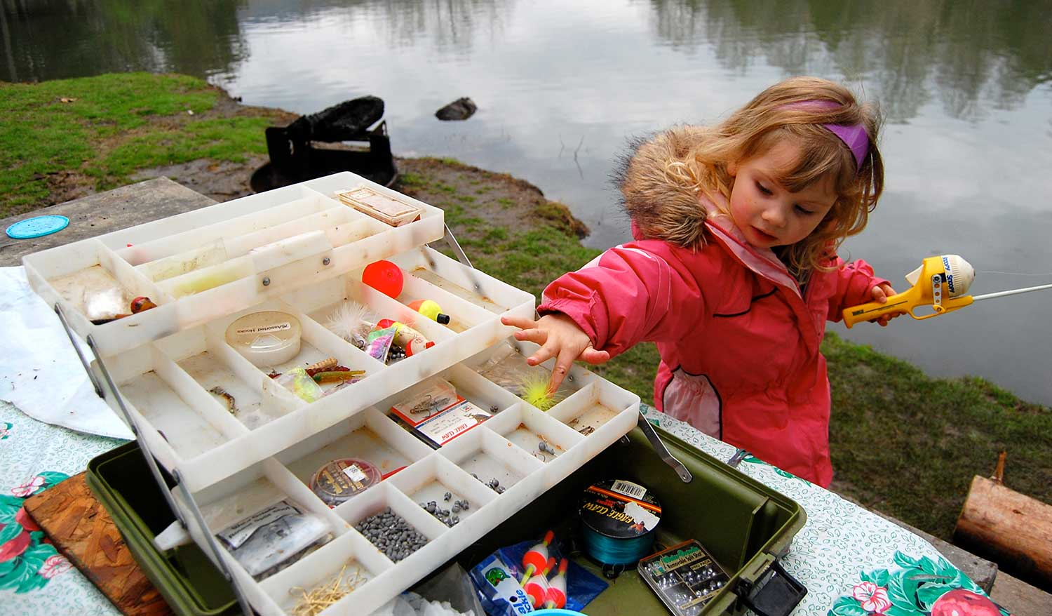 Isabella Ball, 3, examines a fishing lure while camping at Cove Lake State Park. photo by Jordan Vest - 2009