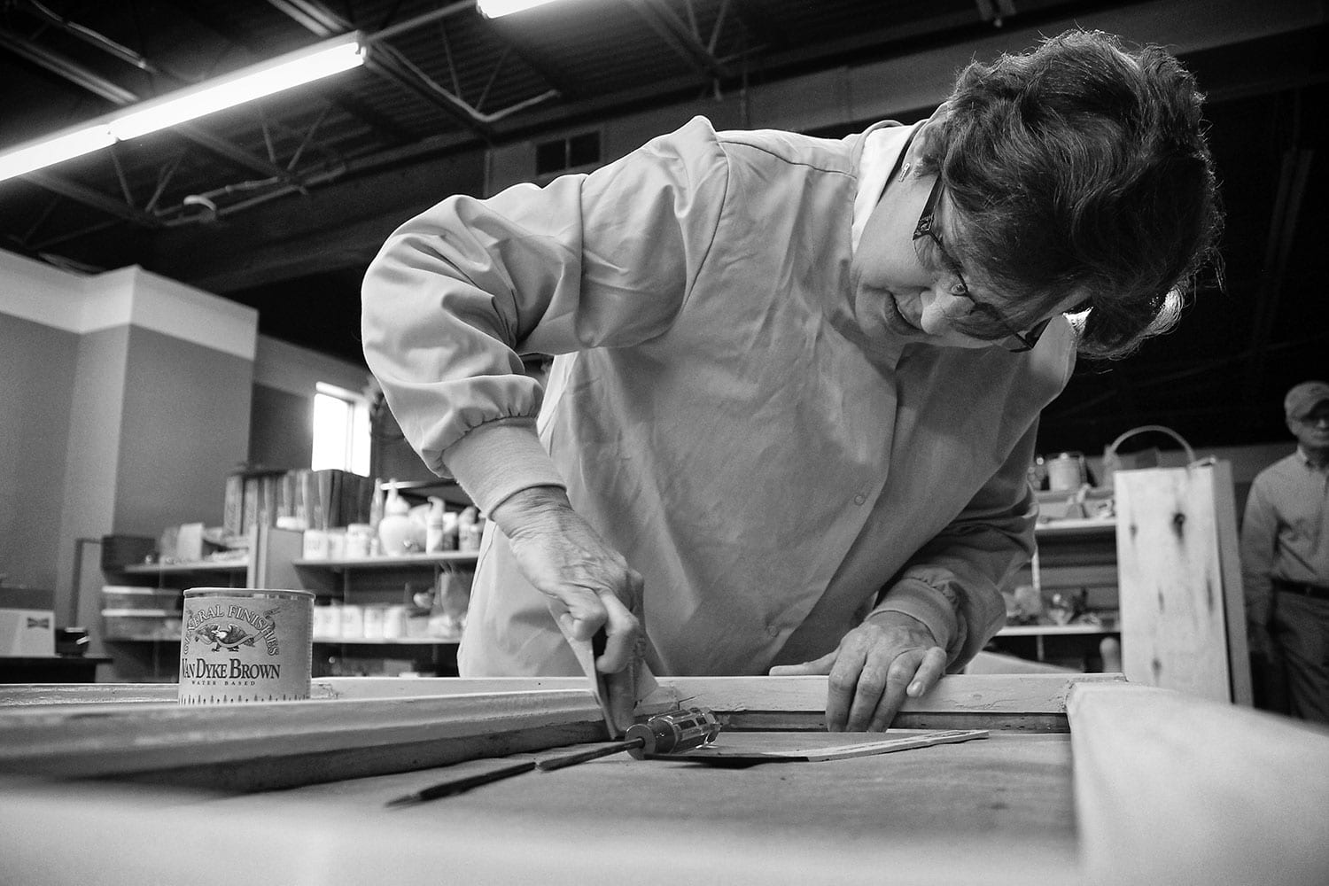 Ann Thompson of Annie's Impressions stains a custom frame for a client. photo by Emilee Lamb - 2015