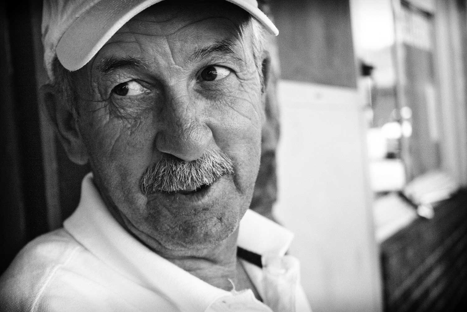 Jimmy Goins relaxes outside of Katie's Carry Out & Catering, which is run by his wife Katie Goins. photo by Nate Patton - 2013