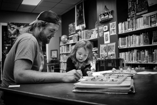 """Ava and her """"Pop Pop"""" Nick Ross, enjoy their time coloring on a rainy morning at the LaFollette Public Library. photo by Haley Guidry - 2019"""