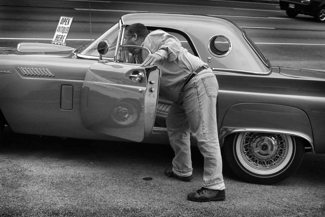 Mark Kitts prepares to pop the hood of one of Crazy Eddie's antique cars. photo by Leigh Imhoff - 2009
