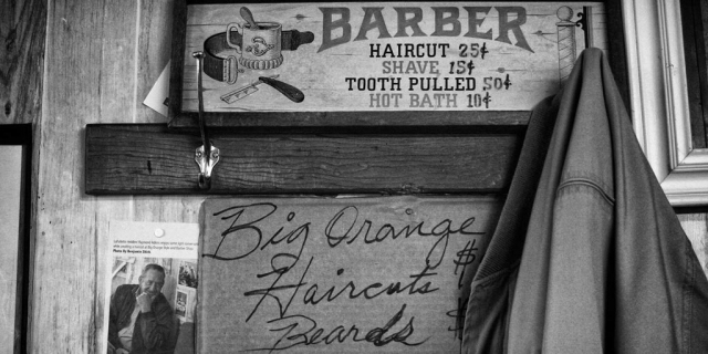 The Big Orange Barber Shop, located on Tennessee Ave., displays its current available services on a piece of cardboard directly below those of many years ago. photo by Ben Moser - 2009