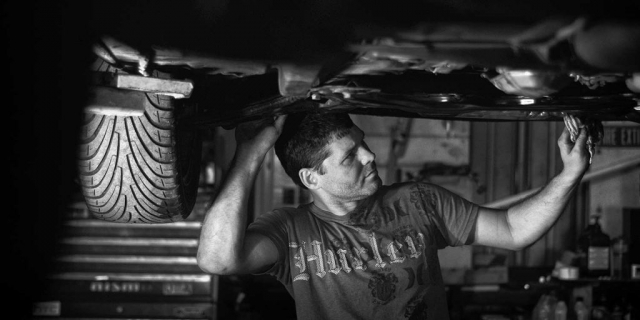 Brandon Johnson scrubs the underside of his car at his personal auto workshop. photo by Logan White - 2014